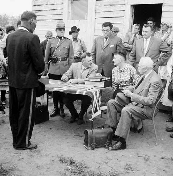 """Governor General's Northern Tour. Governor General Georges P. Vanier and Mrs. Pauline Vanier seated (right) with Indian Agent S.C. Knapp during payment of treaty money to Indians (1961)."" Source: Library and Archives Canada, R1196-14-7-E."