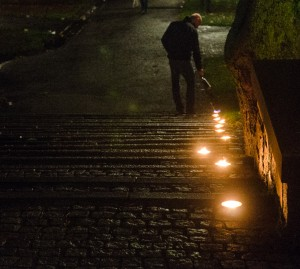 "Man lighting tea lights, ""bringing light to darkness"", downtown Stockholm. Photo credits: J. Luedee"