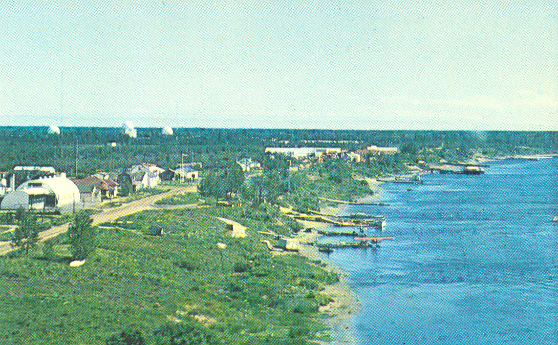 Moosonee c. 1962. Town and Moose River in foreground, radar base and domes in the background. Source: Moosonee Postcards, Paul Lantz website.