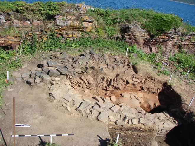 The excavation of the bread oven at Champ Paya (EfAx-09), Cape Rouge Harbour. The outer wall  of the east side can be seen at the bottom of the image. The orange/brown deposits mark the interior of the  oven where baking took place. The oven had been deliberately collapsed when abandoned.