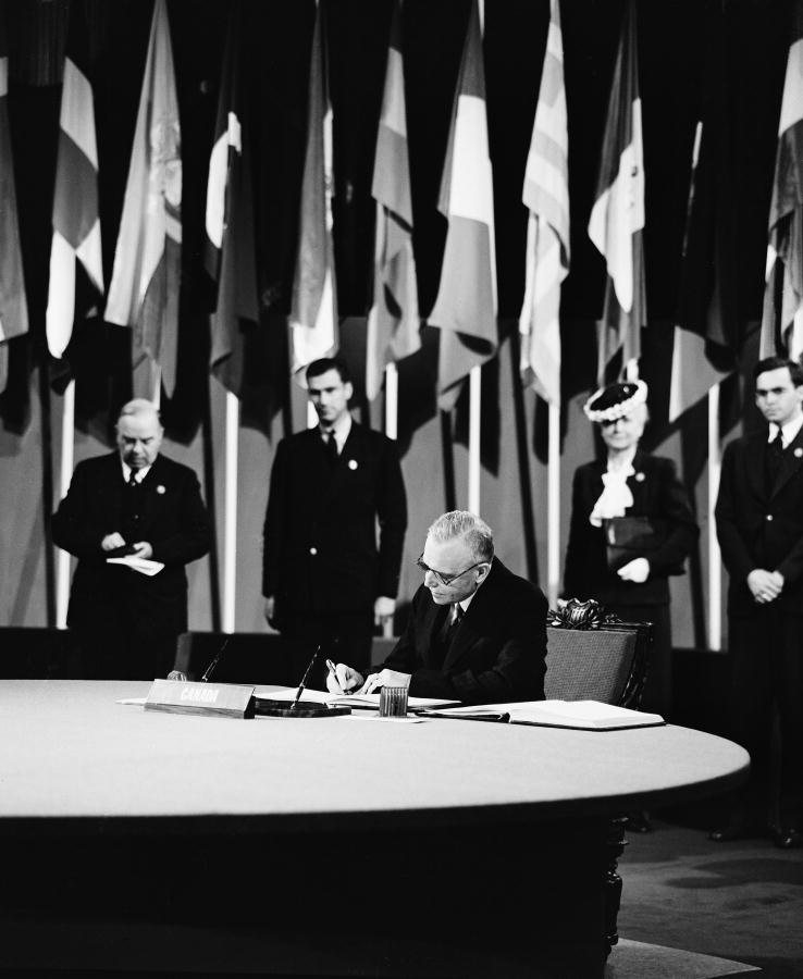 St. Laurent, signing the UN Charter in San Francisco, as Mackenzie King looks on, 26 June 1945.