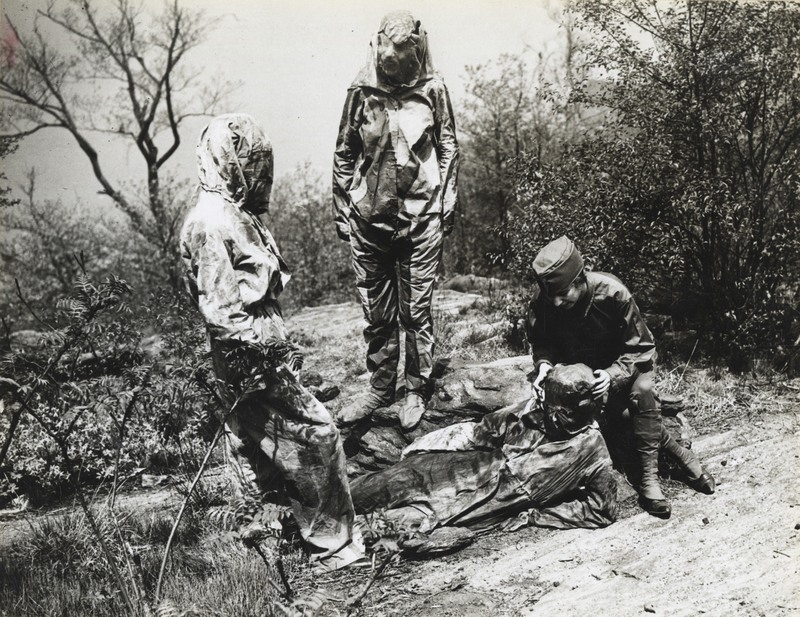 Three camoufleurs in the Women's Reserve Camouflage Corps  make one woman disappear into the forest floor.  (Photo: NARA/165-WW-599G-1); Source: Atlas Obscura