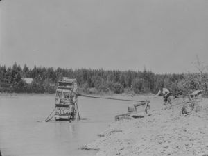 Snipers using water wheels - John Miszzak operates a water wheel outfit, Quesnel River, B.C. Source: Canada. Dept. of Mines and Technical Surveys / Library and Archives Canada / PA-015383
